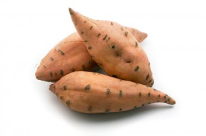 three sweet potatos isolated on white